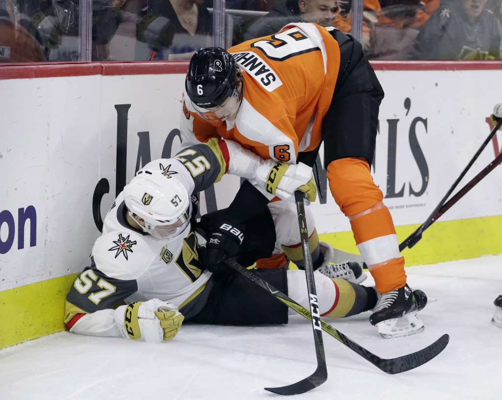 Vegas Golden Knights' David Perron (57) and Philadelphia Flyers' Travis Sanheim (6) battle for the puck during the first period of an NHL hockey game,