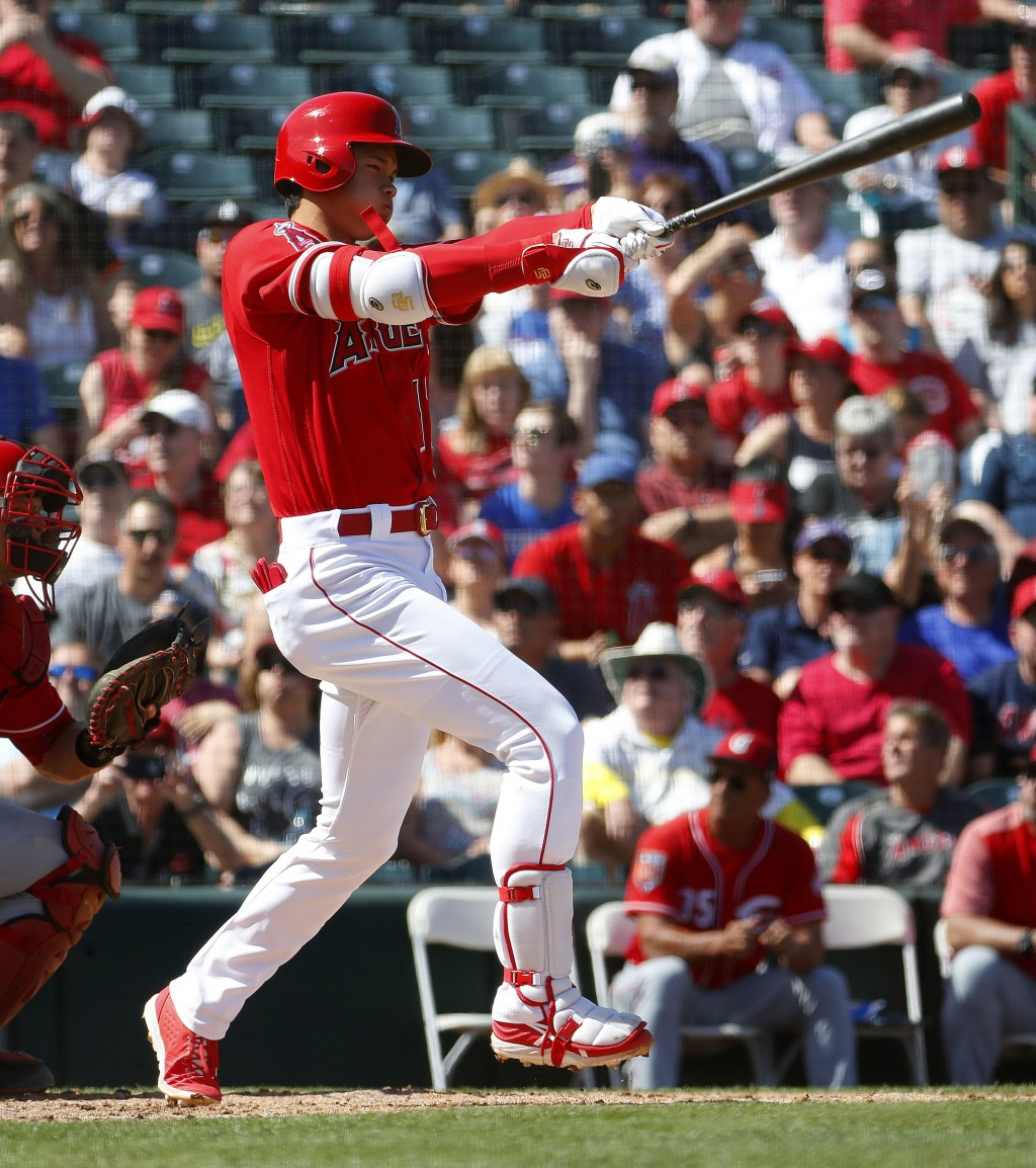 Los Angles Angels' Shohei Ohtani follows through on a foul ball against the Cincinnati Reds during the second inning of a spring training baseball gam
