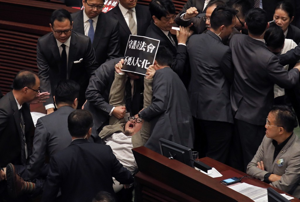 "FILE - In this  Dec. 15, 2017, file photo, pro-democracy lawmaker Shiu Ka-chun holds up a placard reading ""Don't be like China's People's Congress"" wh"
