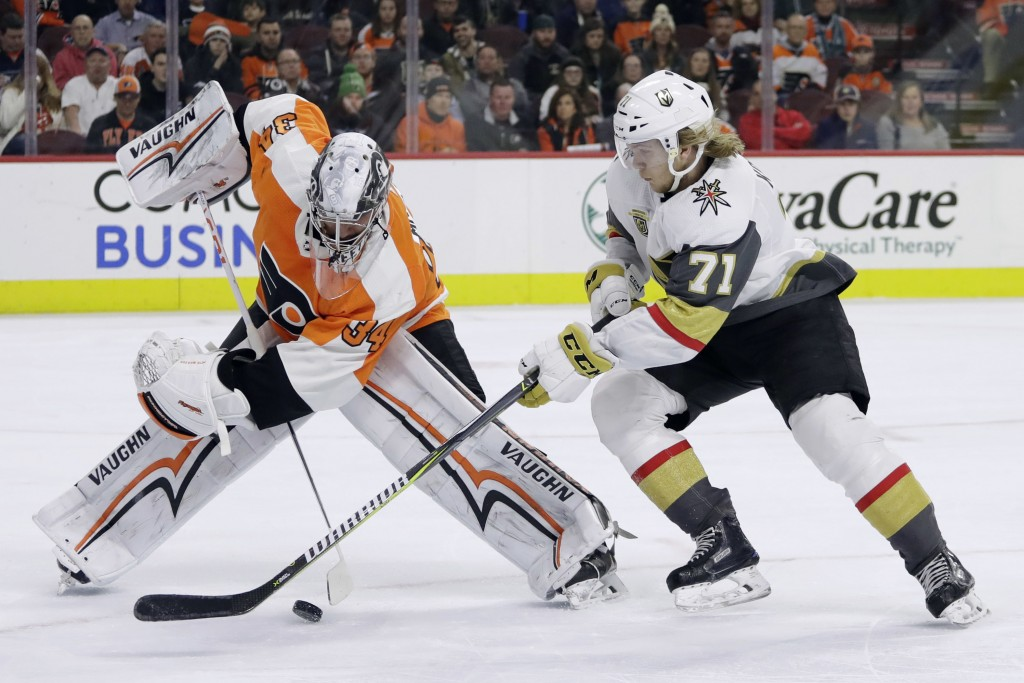 Philadelphia Flyers' Petr Mrazek, left, and Vegas Golden Knights' William Karlsson battle for the puck during the first period of an NHL hockey game,