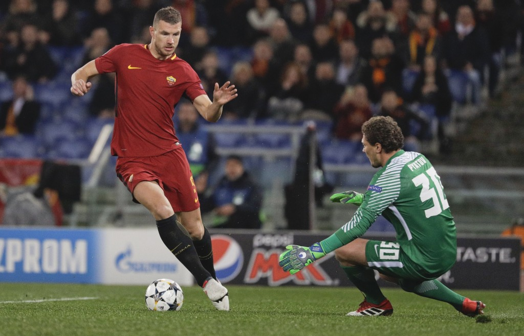 Roma's Edin Dzeko tries to dribble past Shakhtar goalkeeper Andriy Pyatov during a Champions League round of 16 second-leg soccer match between Roma a