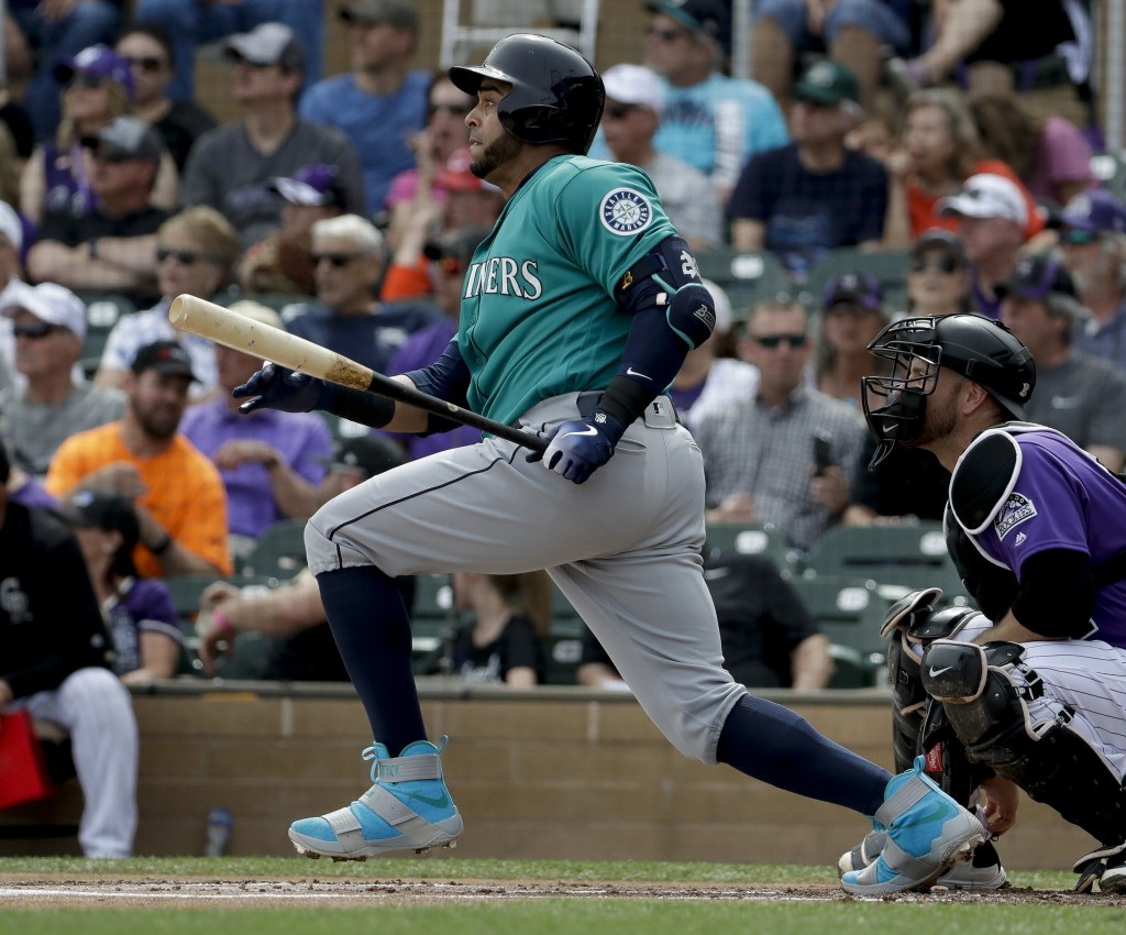Seattle Mariners' Nelson Cruz watches his RBI-single against the Colorado Rockies during the first inning of a spring training baseball game in Scotts