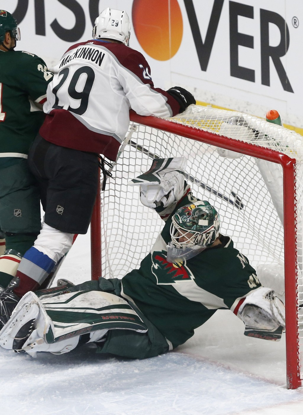 Minnesota Wild goalie Devan Dubnyk winds up on the ice as Colorado Avalanche's Nathan MacKinnon collides with him in the first period of an NHL hockey