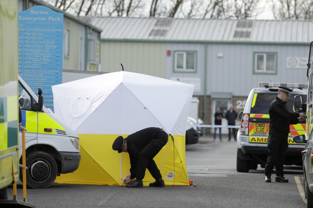 """Police officers position a screen outside the vehicle recovery business """"Ashley Wood Recovery"""" in Salisbury, England, Tuesday, March 13, 2018. The use"""