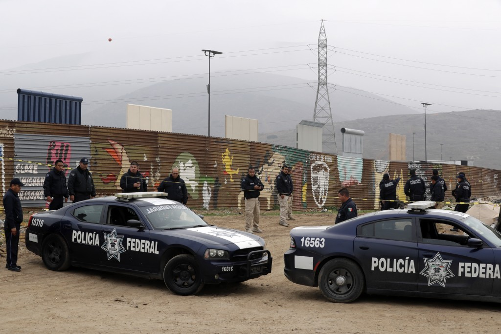 Mexican federal police officers stand guard on the Mexico side of the border on Tuesday, March 13, 2018, in Tijuana, Mexico. President Trump is schedu