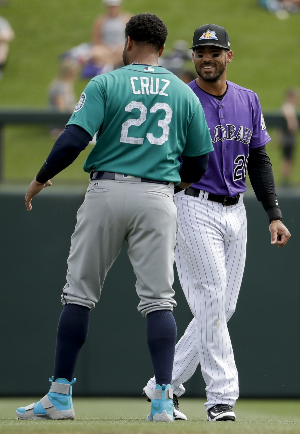 Seattle Mariners designated hitter Nelson Cruz, left, and Colorado Rockies left fielder Ian Desmond chat before a spring training baseball game in Sco