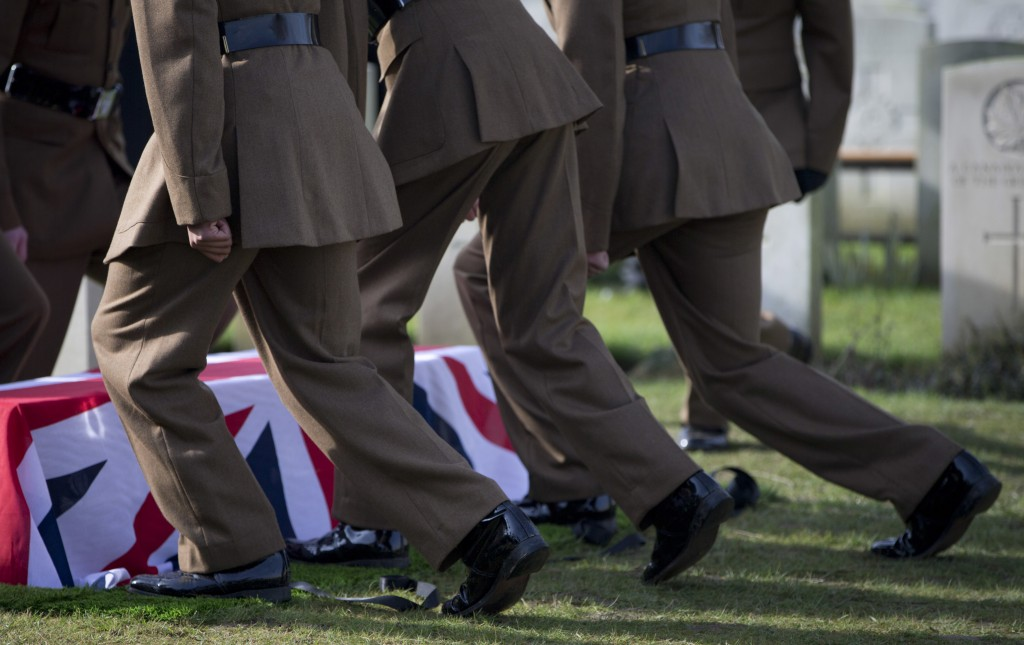 Soldiers prepare to kneel and fold the flag on the casket of British Private Thomas Edmundson during a re-burial service at CWGC Perth Cemetery in Ypr
