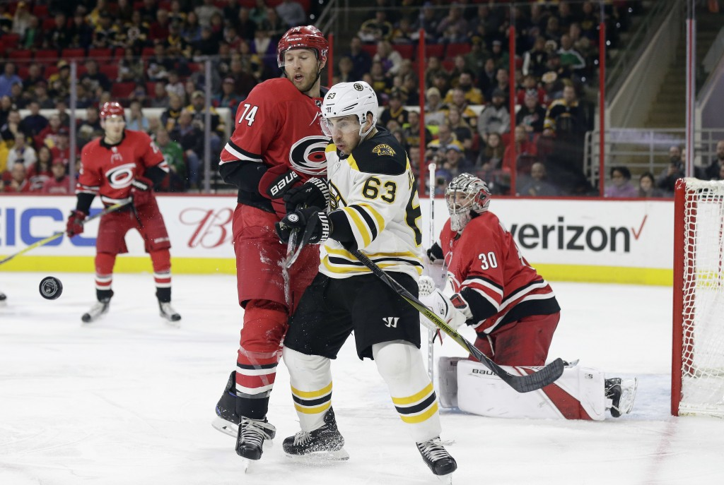 Boston Bruins' Brad Marchand (63) chases the puck with Carolina Hurricanes' Jaccob Slavin (74) as Hurricanes goalie Cam Ward keeps an eye on the puck