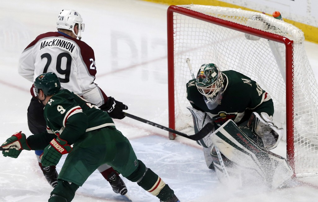 Colorado Avalanche's Nathan MacKinnon, left, scores against Minnesota Wild goalie Devan Dubnyk in the third period of an NHL hockey game, Tuesday, Mar