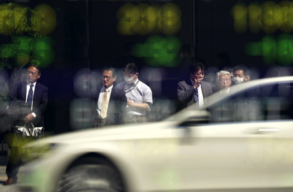 People and a car are reflected on an electronic stock indicator of a securities firm in Tokyo, Wednesday, March 14, 2018. Asian shares fell Wednesday,