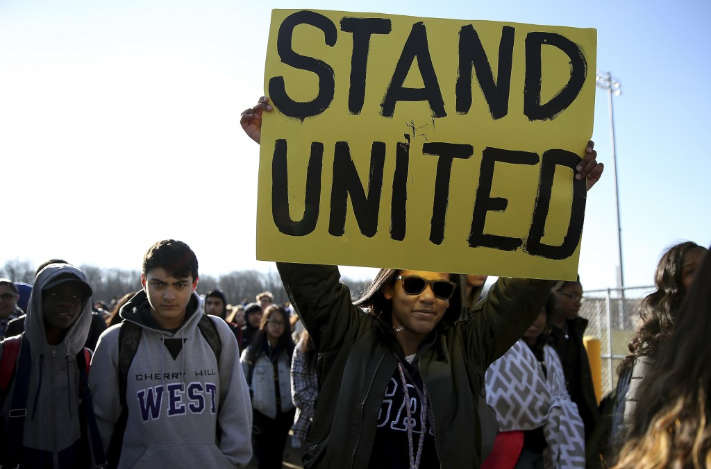 Freshman Kennedi Lawson, 14, carries a sign as student walkout at Cherry Hill West High School in remembrance of those killed in the Parkland, Fla., s