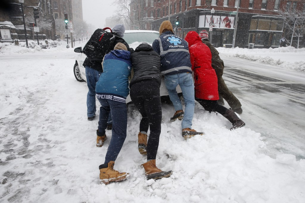 People push a stranded taxi during a snowstorm, Tuesday, March 13, 2018, in Boston.  The third major nor'easter in two weeks slammed New England on Tu
