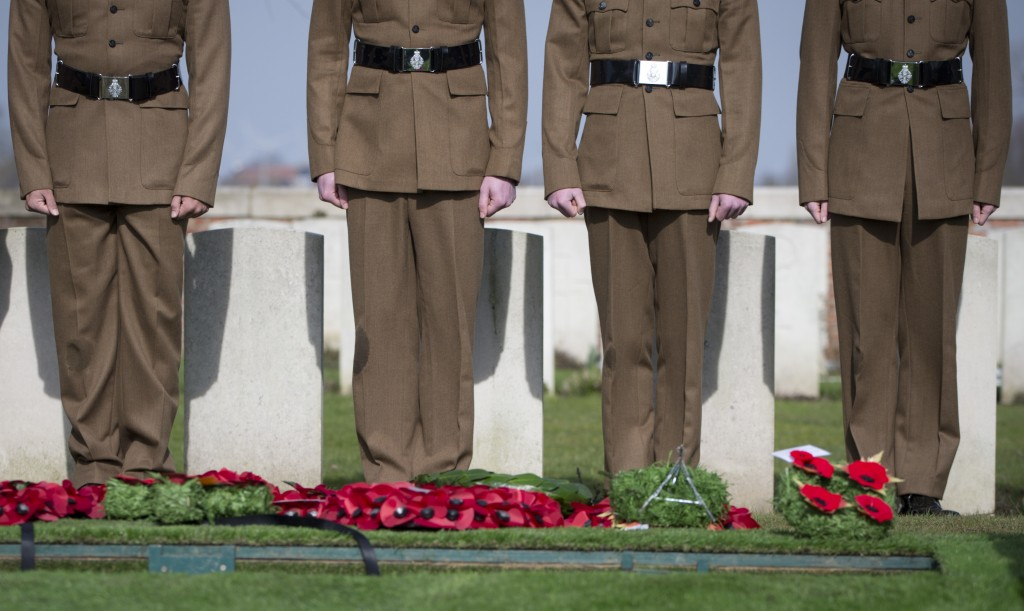 Soldiers stand in front of of the grave of British Private Thomas Edmundson during a re-burial service at CWGC Perth Cemetery in Ypres, Belgium, Wedne