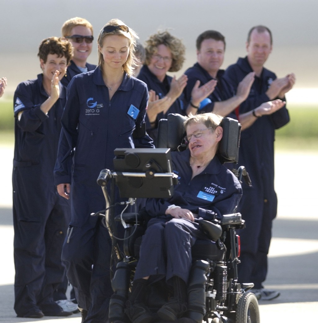FILE - Astrophysicist Stephen Hawking is assisted off the tarmac at the Kennedy Space Center by his caregiver, Monica Guy, as he is applauded by membe