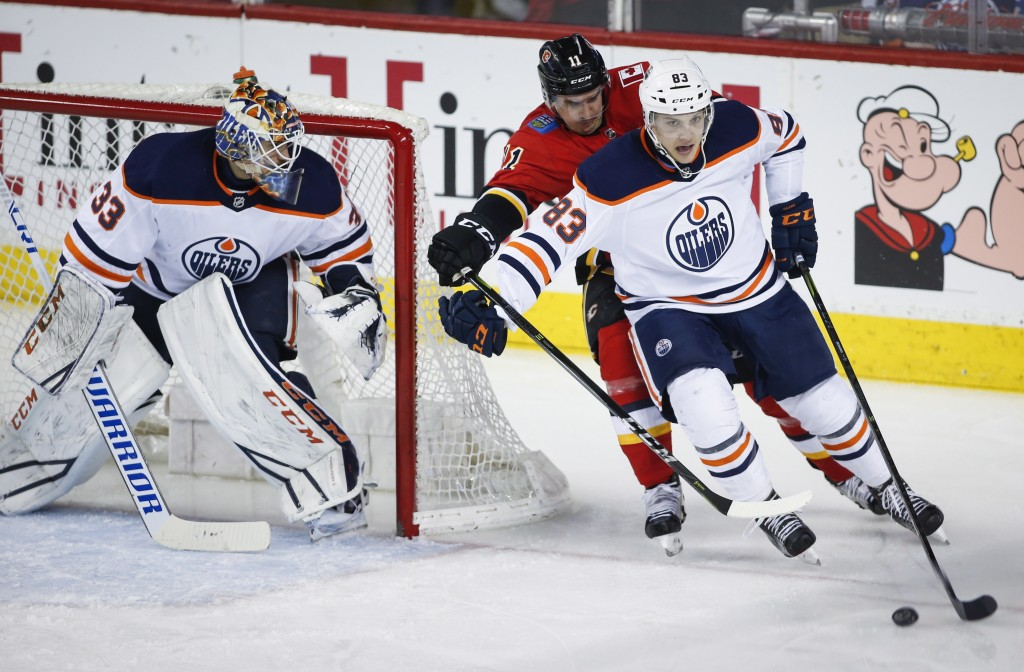 Edmonton Oilers goaltender Cam Talbot (33) looks on as defenseman Matt Benning (83) gets the puck away from Calgary Flames center Mikael Backlund (11)
