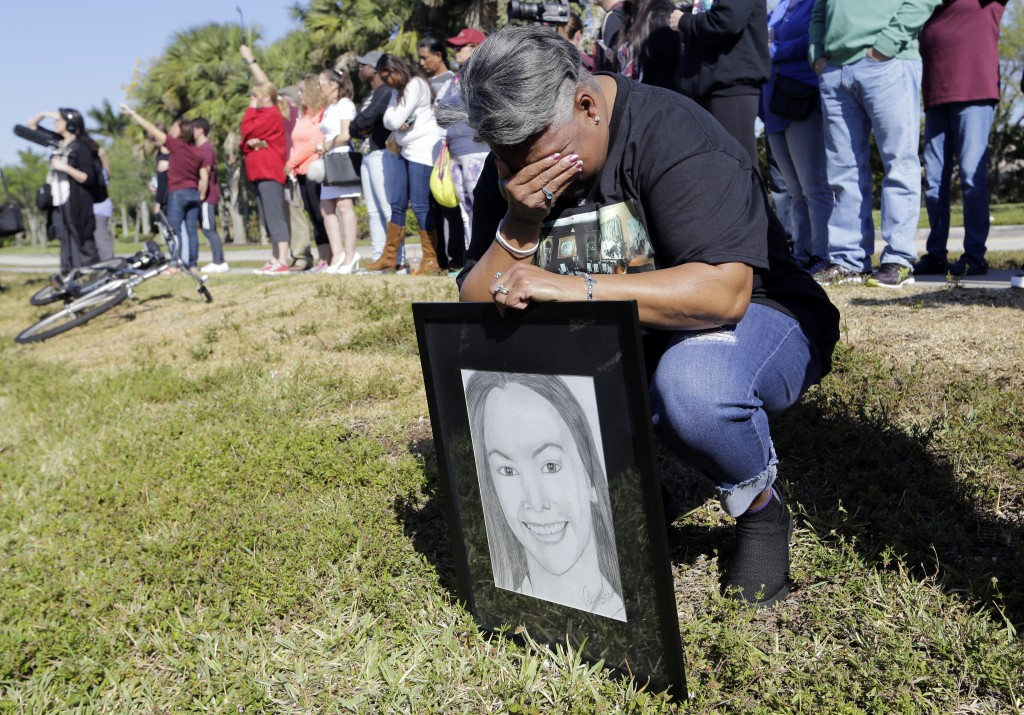 Pat Gibson holds a drawing of Meadow Pollack, a victim of the Marjory Stoneman Douglas High School shooting, as she stands outside of the school as pa