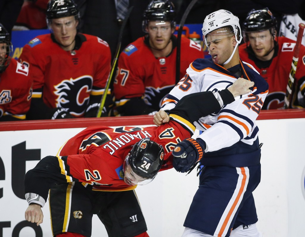 Edmonton Oilers defenseman Darnell Nurse (25) fights with Calgary Flames defenseman Travis Hamonic (24) during the first period of an NHL hockey game
