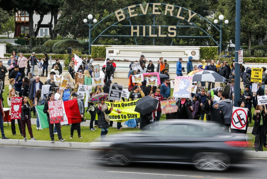 Protesters hold up signs during a rally against a scheduled visit by President Donald Trump Tuesday, March 13, 2018, in Beverly Hills, Calif. Trump is