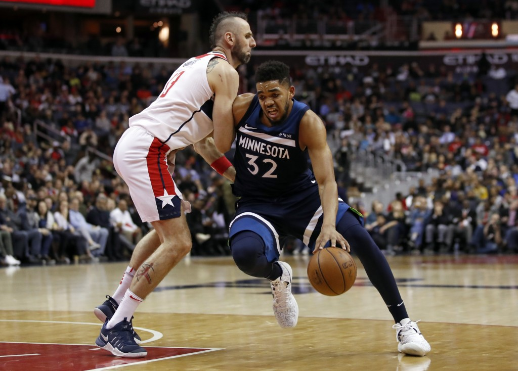 Minnesota Timberwolves center Karl-Anthony Towns (32) drives against Washington Wizards center Marcin Gortat (13), from Poland, during the first half