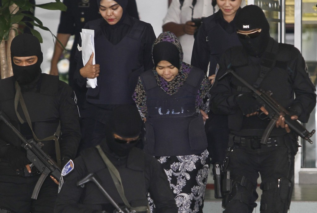 Indonesian Siti Aisyah, second from right, is escorted by police as she leaves a court hearing at Shah Alam High Court in Shah Alam, Malaysia, Wednesd