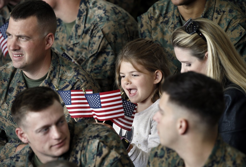 A youngster plays with flags while waiting for President Donald Trump to speak at Marine Corps Air Station Miramar, in San Diego, Tuesday, March 13, 2