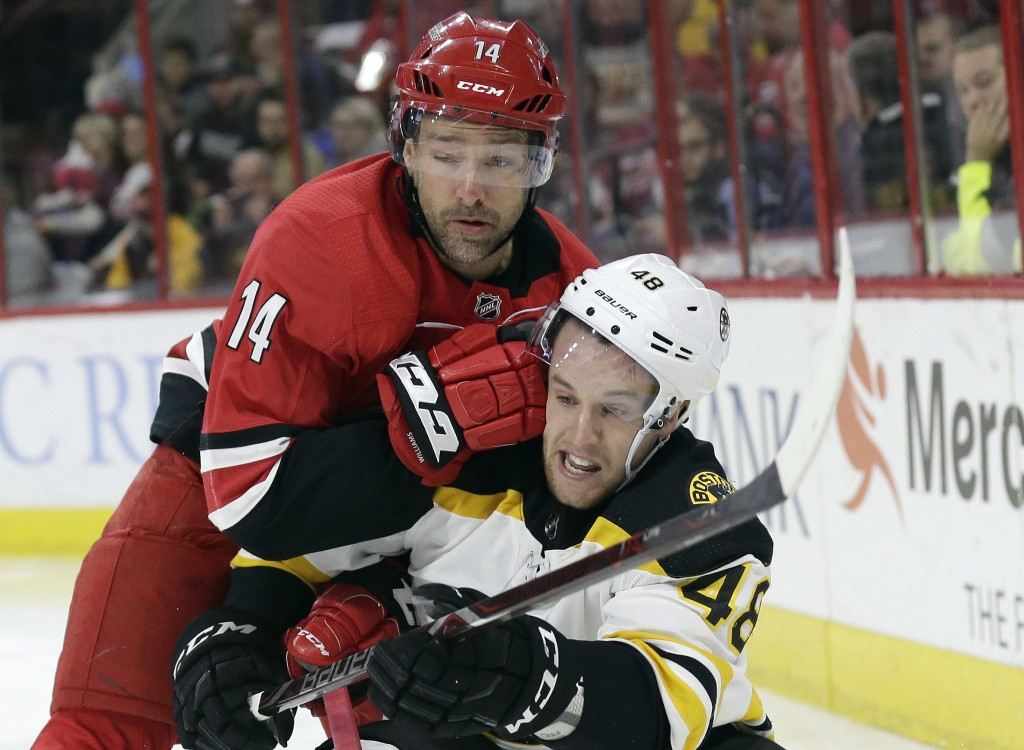 Boston Bruins' Matt Grzelcyk (48) and Carolina Hurricanes' Justin Williams (14) make contact while chasing the puck during the second period of an NHL