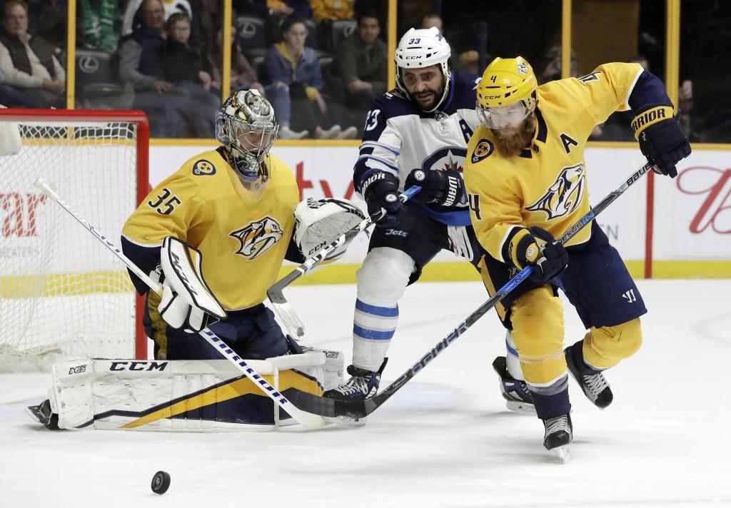 Winnipeg Jets' Dustin Byfuglien (33) and Nashville Predators' Ryan Ellis (4) chase a rebound after Predators goalie Pekka Rinne (35), of Finland, bloc