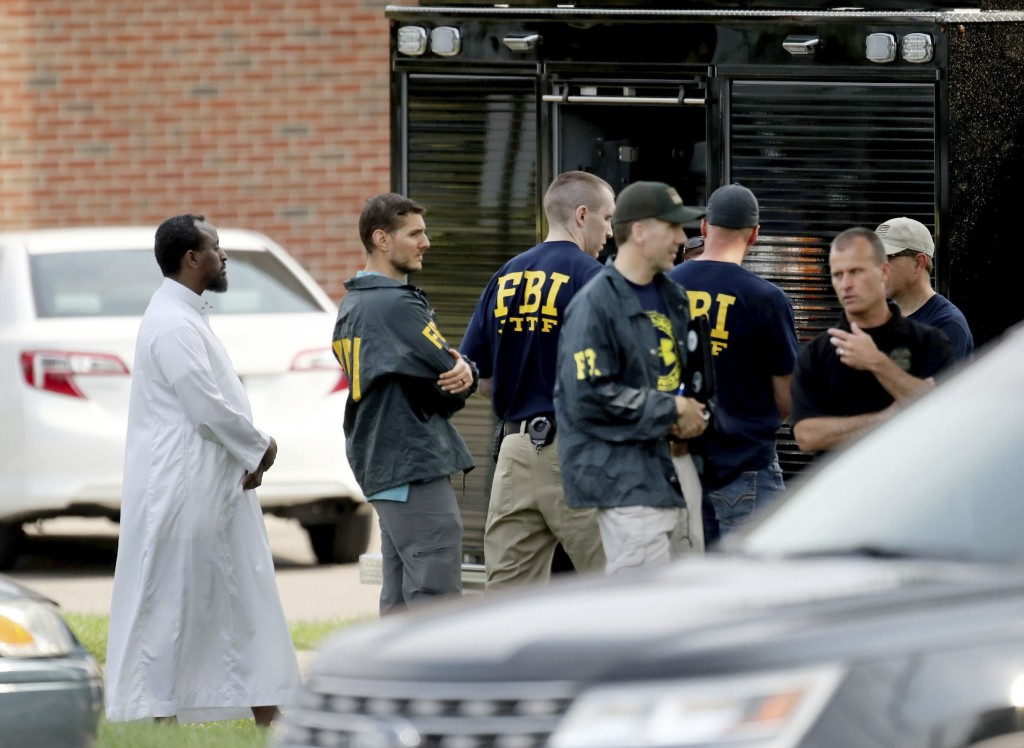 FILE - In this Aug. 15, 2017 file photo, Law enforcement officials investigate an explosion at the Dar Al-Farooq Islamic Center in Bloomington, Minn.