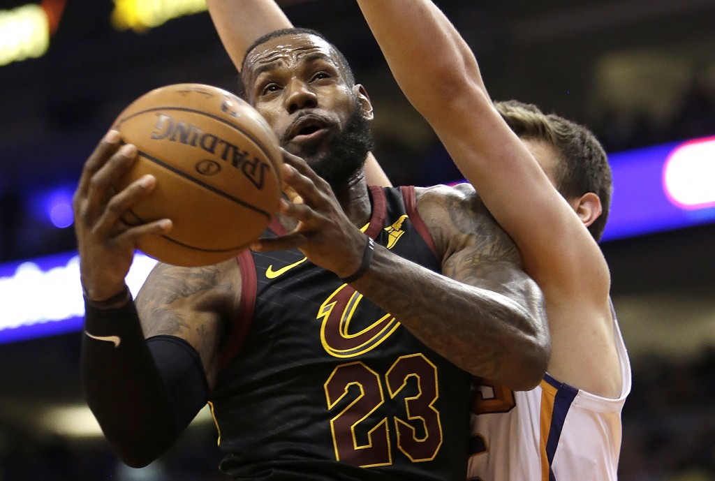 Cleveland Cavaliers forward LeBron James (23) gets fouled by Phoenix Suns forward Dragan Bender in the first half of an NBA basketball game, Tuesday,