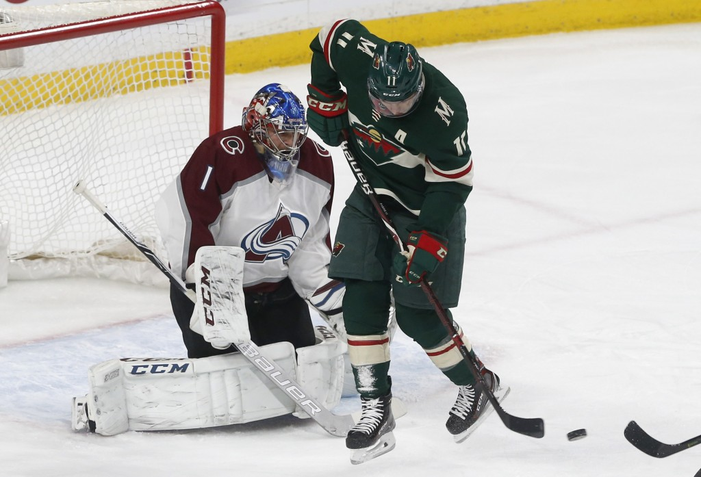 Minnesota Wild's Zach Parise, right, waits for the pass as Colorado Avalanche goalie Semyon Varlamov, of Russia, defends in the first period of an NHL