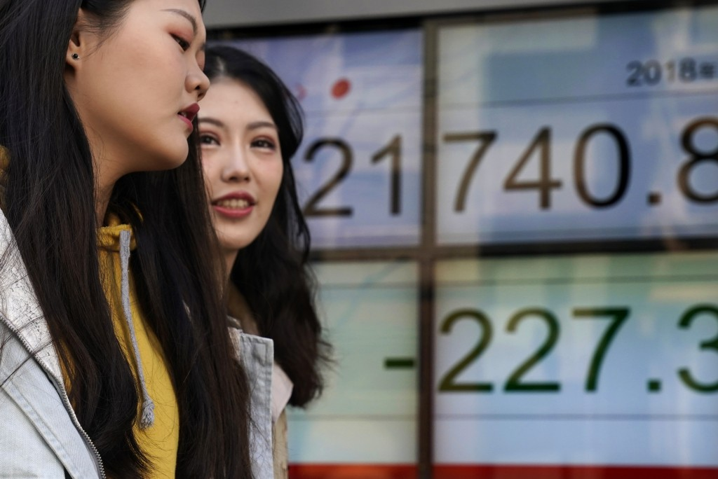Women walk past an electronic stock indicator of a securities firm in Tokyo, Wednesday, March 14, 2018. Asian shares fell Wednesday, taking their cue