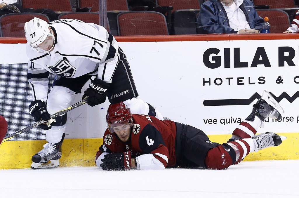 Los Angeles Kings center Jeff Carter (77) sends Arizona Coyotes defenseman Niklas Hjalmarsson (4) to the ice during the first period of an NHL hockey