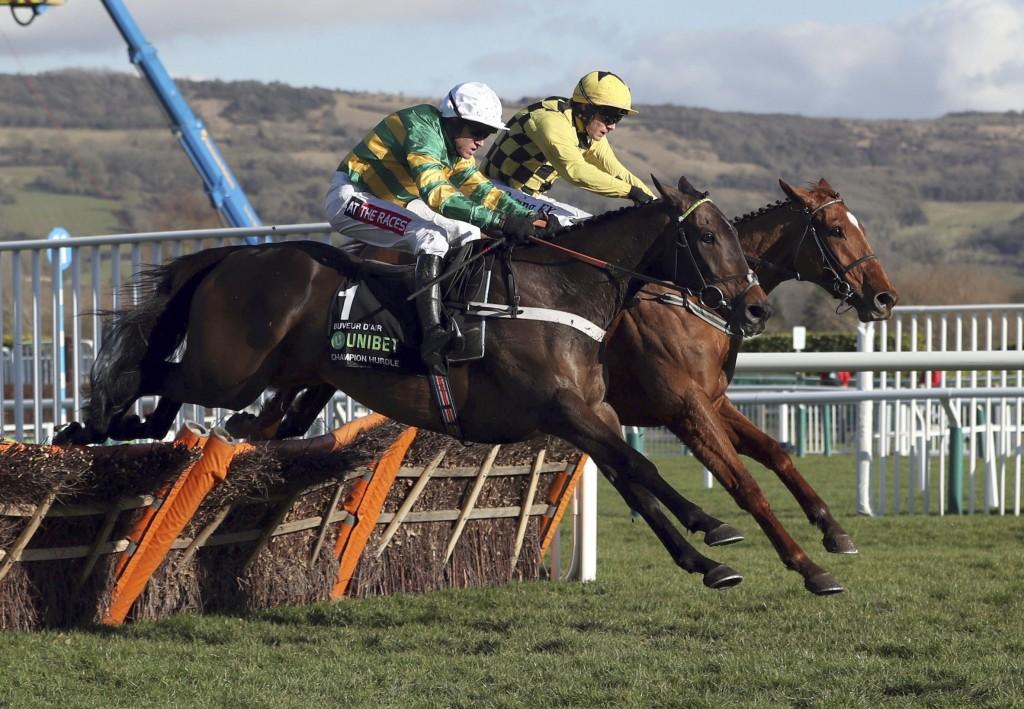 Race winner Buveur D'Air ridden by Barry Geraghty, foreground, clears the last hurdle alongside Melon, ridden by Paul  Townend,  as they race  to fini