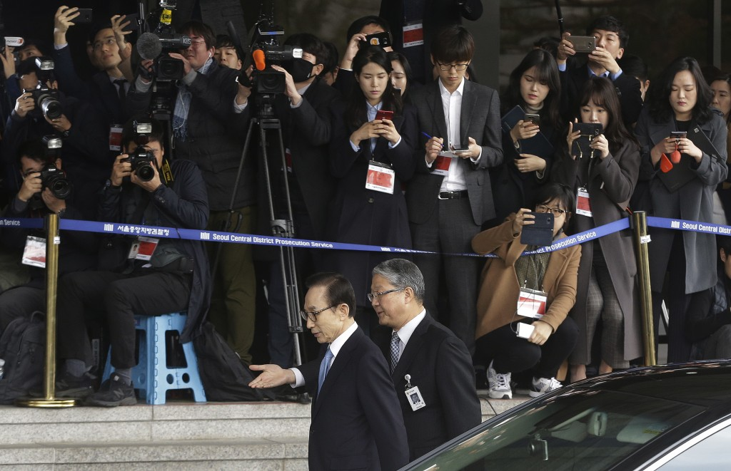 Former South Korean President Lee Myung-bak, center left, is escorted upon arrival for questioning over bribery allegations at Seoul Central District