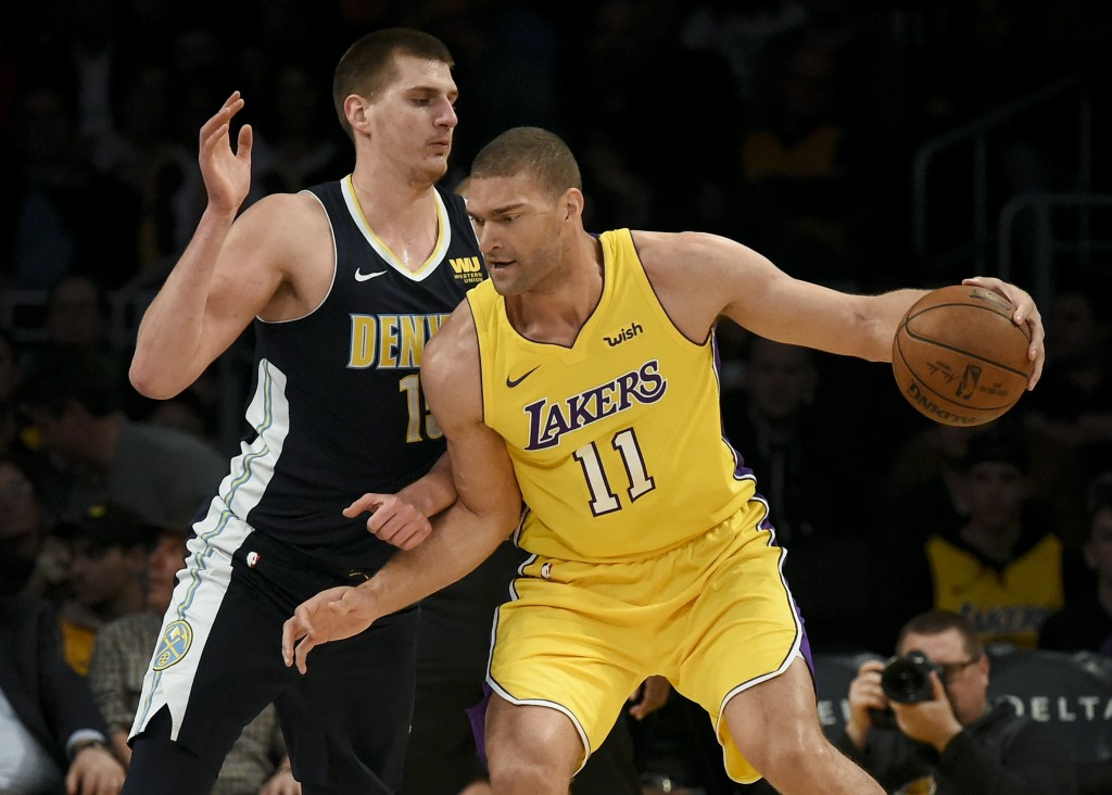 Los Angeles Lakers center Brook Lopez, right, posts up on Denver Nuggets center Nikola Jokic during the first half of an NBA basketball game in Los An