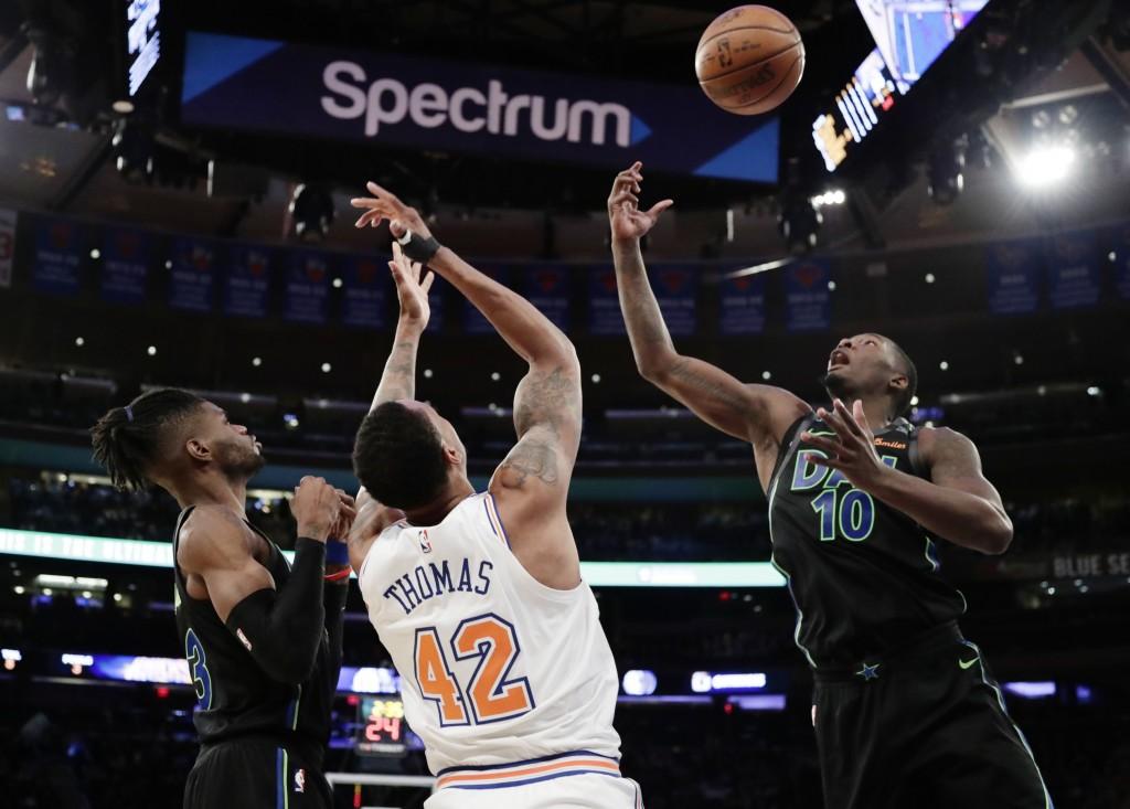 Dallas Mavericks' Dorian Finney-Smith (10) fights for control of the ball with New York Knicks' Lance Thomas (42) as teammates Nerlens Noel defends du