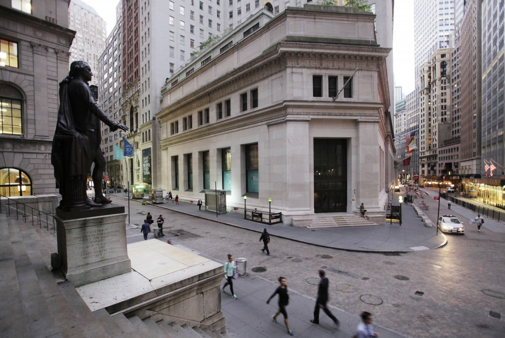 FILE - In this Oct. 8, 2014, file photo, people walk to work on Wall Street beneath a statue of George Washington, in New York. The U.S. stock market