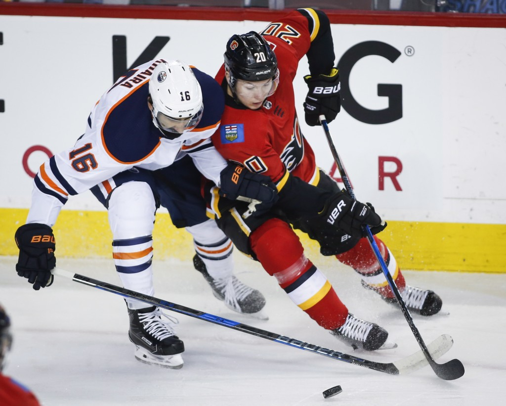Edmonton Oilers left wing Jujhar Khaira (16) fights for the puck with Calgary Flames centre Curtis Lazar (20) during the first period of an NHL hockey