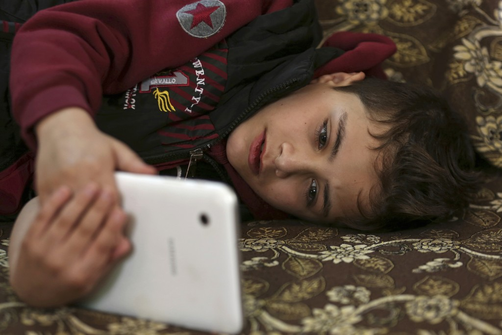 In this March 6, 2018 photo, Syrian refugee Younis al-Hariri, 8, looks at a mobile phone in his home in Amman Jordan. Younis was diagnosed with cystic