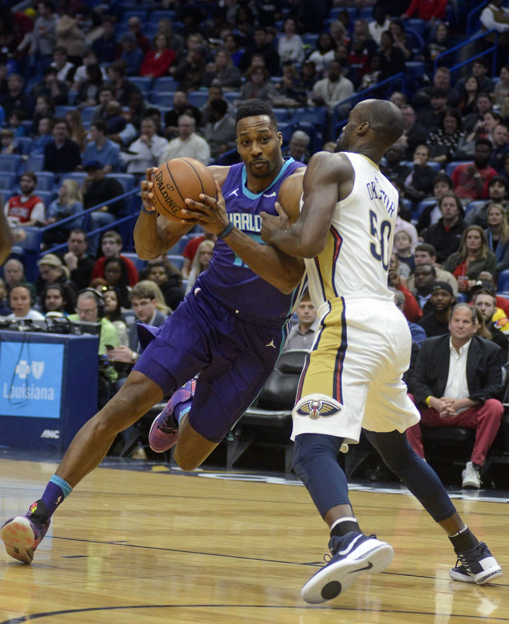 Charlotte Hornets' Dwight Howard, left, drives to the basket against New Orleans Pelicans center Emeka Okafor in the first half of an NBA basketball g