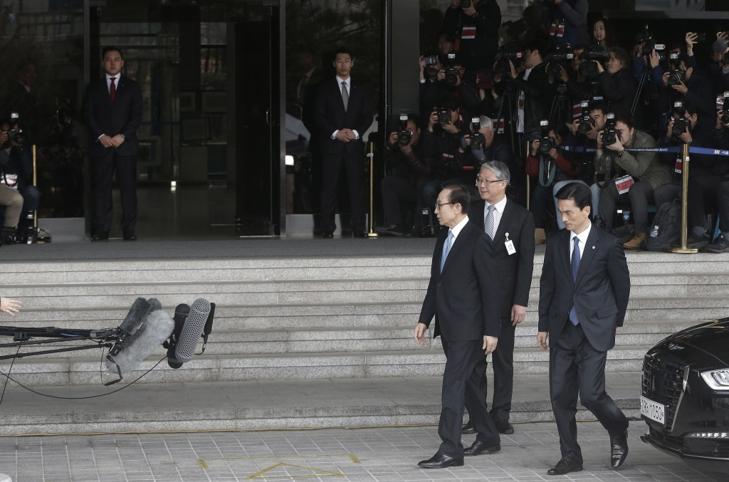 Former South Korean President Lee Myung-bak, third from right, arrives for questioning over bribery allegations at the Seoul Central District Prosecut