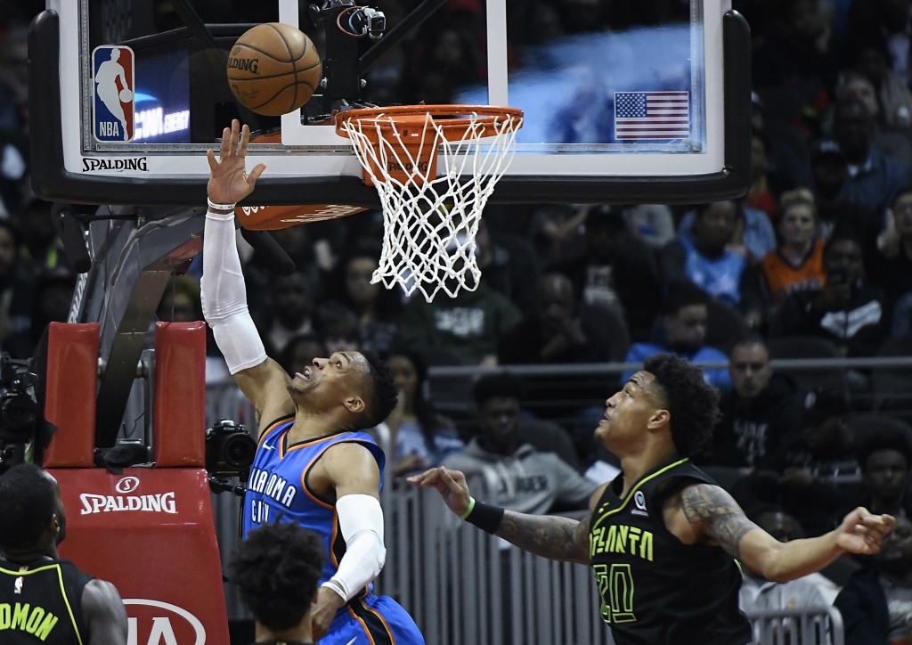 Oklahoma City Thunder guard Russell Westbrook shoots a reverse layup as Atlanta Hawks forward John Collins (20) defends during the first half of an NB