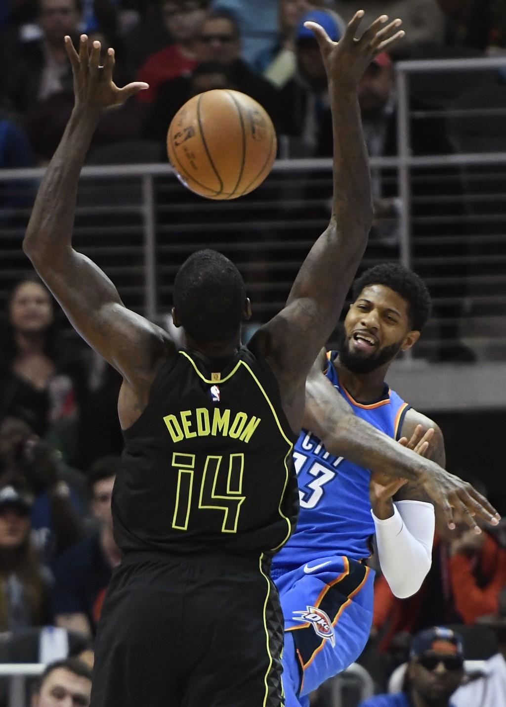 Oklahoma City Thunder forward Paul George sends a pass through the arms of Atlanta Hawks center Dewayne Dedmon (14) during the first half of an NBA ba