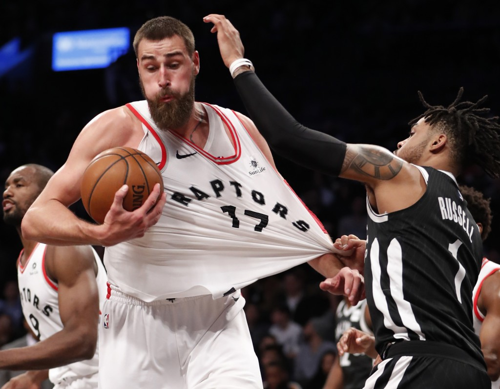 Brooklyn Nets guard D'Angelo Russell, right, grabs the jersey of Toronto Raptors center Jonas Valanciunas (17), for which he drew a foul call, Tuesday