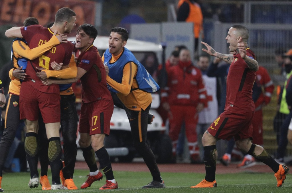 Roma's Edin Dzeko, left, celebrates with teammates after scoring his side's opening goal during a Champions League round of 16 second-leg soccer match