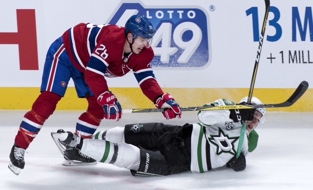 Montreal Canadiens defenseman Mike Reilly (28) sends Dallas Stars centre Tyler Pitlick (18) to the ice during the second period of an NHL hockey game