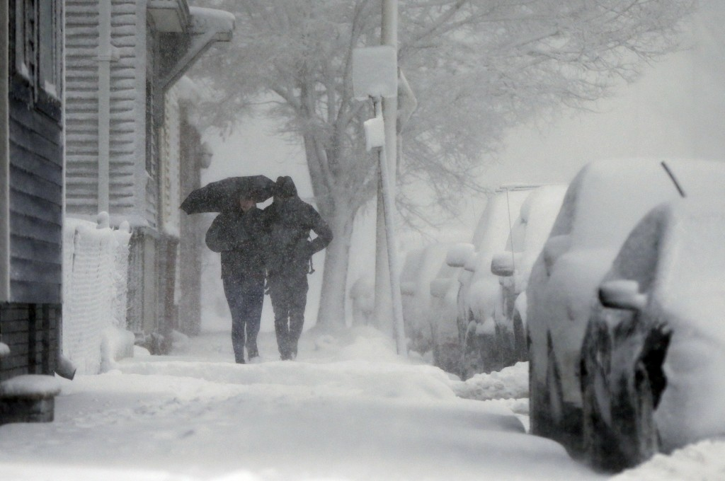 A couple walks on Marginal Street in Boston, Tuesday, March 13, 2018. The National Weather Service issued a blizzard warning for much of the coast of