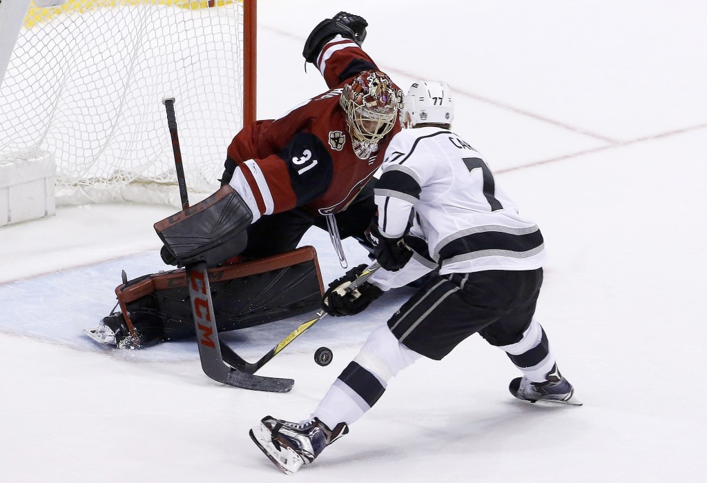 Arizona Coyotes goaltender Adin Hill (31) makes a save on a shot by Los Angeles Kings center Jeff Carter (77) during a shootout of an NHL hockey game