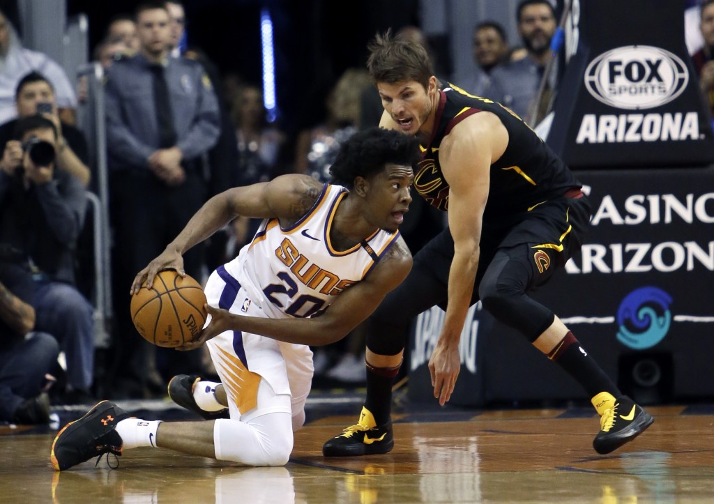 Phoenix Suns guard Josh Jackson (20) and Cleveland Cavaliers guard Kyle Korver battle for a loose ball in the first half of an NBA basketball game, Tu
