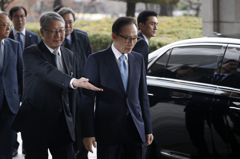 Former South Korean President Lee Myung-bak, third from left, is escorted upon arrival for questioning over bribery allegations at the Seoul Central D